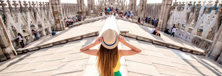 Back-view-on-the-female-traveler-standing-on-the-rooftop-of-Duomo-cathedral-in-Milan.-Having-great-vacations-in-Milan_481189675