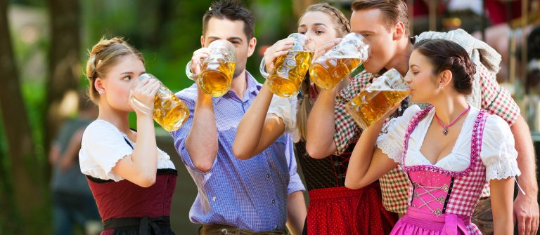 In-Beer-garden-in-Bavaria-Germany-friends-in-Tracht-Dirndl-and-Lederhosen-and-Dirndl-standing-in-front-of-band_shutterstock_138936287