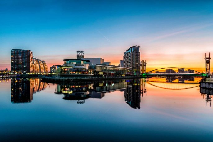 A winter orange sunrise at Salford Quays with clear reflections in the water.