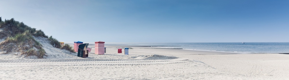 Beach chairs on the island of Borkum with sand and a blue sky